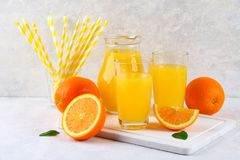 Glass cups and a pitcher of fresh orange juice with slices of orange and yellow tubes on a light gray table. Glass cups and a pitcher of fresh orange juice with royalty free stock images