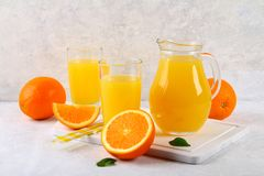 Glass cups and a pitcher of fresh orange juice with slices of orange and yellow tubes on a light gray table. Glass cups and a pitcher of fresh orange juice with royalty free stock image