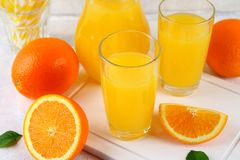 Glass cups and a pitcher of fresh orange juice with slices of orange and yellow tubes on a light gray table. Glass cups and a pitcher of fresh orange juice with stock photo
