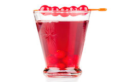 Glass currant liqueur. A glass of currant liqueur with fresh currants on a cocktail stick royalty free stock photography