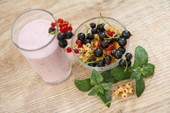 Glass of currant yogurt  with fresh berries of red, black, white Royalty Free Stock Image