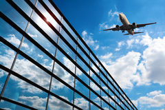 Glass curtain wall and aircraft. Against a blue sky Royalty Free Stock Photos