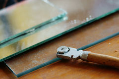 Glass cutter and glass sheet on wooden background Stock Images