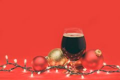 Glass of dark ale or porter beer with christmas lights and baubles on red background. Snifter glass of dark ale or porter beer with christmas lights and baubles stock images