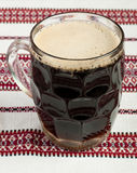 Glass of dark beer. A glass of beer on the table, Glass of dark beer glass on the tablecloth, A glass of dark beer, Black beer on rushnyk, A glass of beer on a Royalty Free Stock Photo