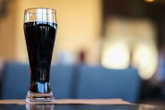 Glass of dark beer in bar or in pub close up. Real scene. Concept of beer culture, Craft brewery, uniqueness of beer royalty free stock photography