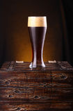 Glass of dark beer on a chest Stock Photo