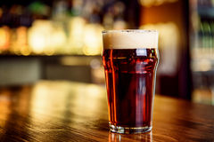 A glass of dark beer on counter Stock Photography