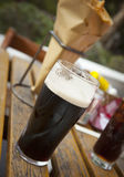 Glass of dark beer fish and chips. Royalty Free Stock Photos