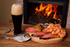 Glass of dark beer and a fish platter on the background of a bur Royalty Free Stock Photos