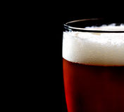 Glass of dark beer with foam on a black background Stock Photography
