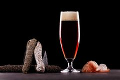 A glass of dark beer foam, Parma ham, expensive varieties of sausage. On black background. Place for logo royalty free stock photos