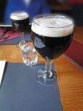 Glass of dark beer on restaurant table. In ski resort at Chatel, France Stock Image