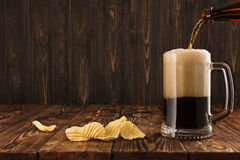 Glass with a dark beer on a wooden table.  stock images