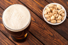 Glass of dark cold frothy beer, nuts old wooden table Stock Image