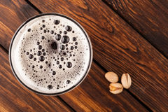 Glass of dark cold frothy beer, nuts old wooden table Stock Photos