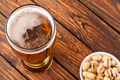 Glass of dark cold frothy beer, nuts old wooden table. Glass of dark cold frothy beer, nuts on an old wooden table. top view Stock Photos