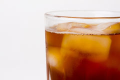 Glass with dark liquid full with ice cubes. Glass with ice tea full with ice cubes on white background Stock Photos