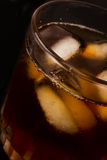 Glass with dark liquid full with ice cubes Stock Photo