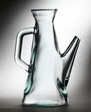 Glass decanter. Close-up on a glass decanter on grey, lit background Royalty Free Stock Photography