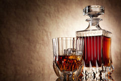 Glass and decanter of brandy on a old stone backgr Stock Photography