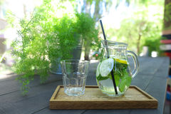 Glass decanter and glass faceted cup stands on plank on table in Stock Photos