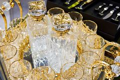 Glass decanters and glasses for drinks with golden decor. Glass decanters and glasses for drinks decorated with gold Stock Photo