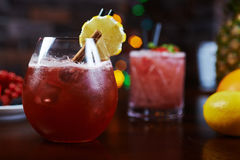 Glass of delicious alcoholic cocktails or lemonade with ice, decoration of fresh berries and a slice of lemon on a wooden table in Royalty Free Stock Photography