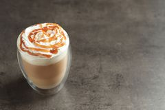 Glass with delicious caramel frappe. On grey background Stock Image