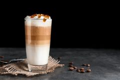 Glass with delicious caramel frappe. On table Royalty Free Stock Images