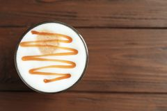 Glass with delicious caramel latte. On wooden background Royalty Free Stock Photography