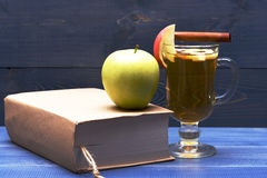 Glass of delicious glintwein with apple and book Royalty Free Stock Photography