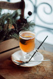 Glass of delicious orange glintwein or mulled hot wine thread on vintage wooden winter background Royalty Free Stock Photos