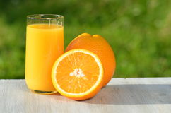 Glass of delicious orange juice and oranges on table Royalty Free Stock Photo