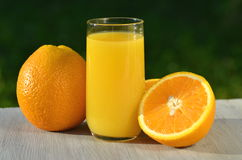 Glass of delicious orange juice and oranges on table Stock Image