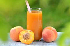 Glass of delicious peach juice and peaches on table Stock Photo