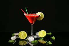 Glass of delicious strawberry daiquiri with lime. And ice cubes on black background Royalty Free Stock Images