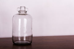 Glass demijohn against a light background Stock Photos
