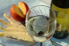 Glass of desert white wine with cheese and fruit, closeup. Closeup on glass of white wine with bottle and glass plate with cheese and peach on a background Stock Image