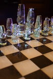 Glass designer chess pieces. Glass chess pieces set out on the board with selective focus and black background Stock Photo