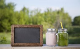 Glass of detox smoothie and blackboard on wooden table in the ga Stock Photos