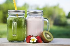 Glass of detox smoothie and fruit on wooden table in the garden. With fruit Stock Image