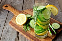 Glass of detox water with lemon, cucumber on serving board Royalty Free Stock Photo