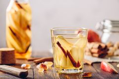 Water with Pear, Cinnamon, Ginger. Glass of Detox Water with Sliced Pear, Cinnamon Stick, Ginger Root and Some Sugar. Ingredients on Wooden Table and Bottle of Stock Images