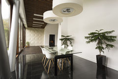 Glass dining table and white chairs Stock Photos