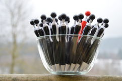 A glass dish with black globule ballpoint pens with a red one