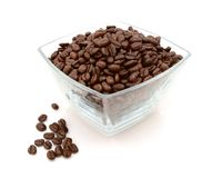 Glass dish filled with coffee beans, some spilled beside. Glass dish filled with roasted coffee beans with some spilled beside on a white background Royalty Free Stock Photography