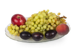Glass dish with grapes, plums, peaches and apples Stock Image