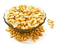 Glass dish with tasty peanuts. Glass dish with peanuts on white background closeup Stock Photography