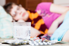 Glass with dissolved drug in water and pills. Glass with dissolved drug in water and pile of pills on table close up and sick girl with scarf around her neck on Royalty Free Stock Image